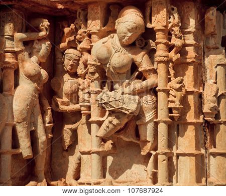 Woman beats the drum on the front of Hindu temple in India