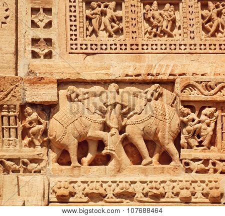 Indian elephants of massive stone bas-relief on the front of historical wall of temple, India