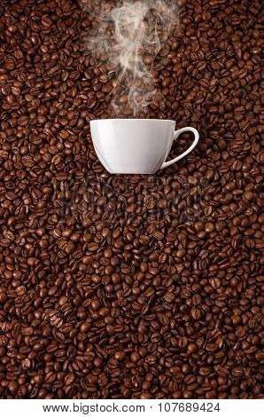 White cup with hot steam smoke at coffee beans background
