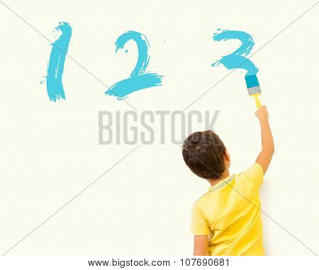 Llittle boy painting numbers 123 with brush on the wall - Almost Finished