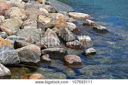 Rock bed along shoreline of clear blue lake waters