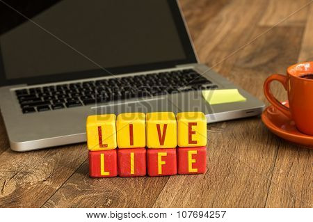 Live Life written on a wooden cube in a office desk
