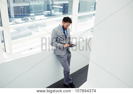Successful manager using touch pad to prepare for working day while standing in office space