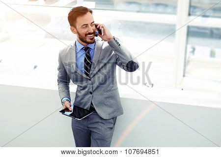 Young successful men entrepreneur speaking on mobile phone during work on digital tablet