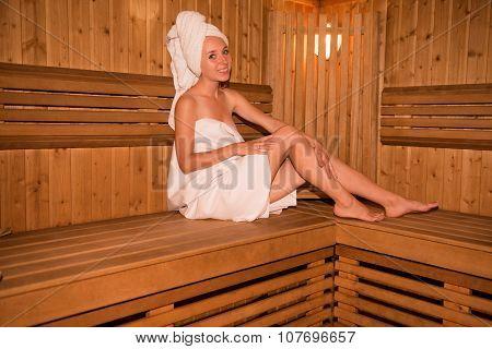 Beautiful Girl In Towel Sitting On The Bench In Sauna