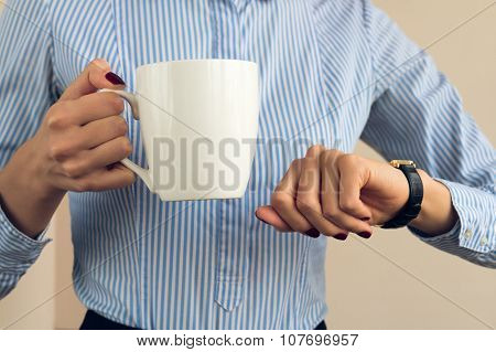 Woman With A Burgundy Manicure In A Blue Striped Shirt Holds A White Cup And Looking At Her Watch