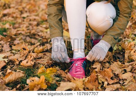 Woman Tying Shoelaces On Sneakers During An Autumn Walk In The Park
