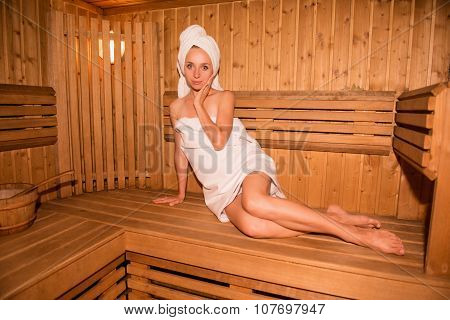 Nice-looking Girl In Towel Sitting On The Bench In Sauna