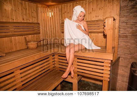 Surprised Funny Girl In Towel Sitting On The Bench In Sauna