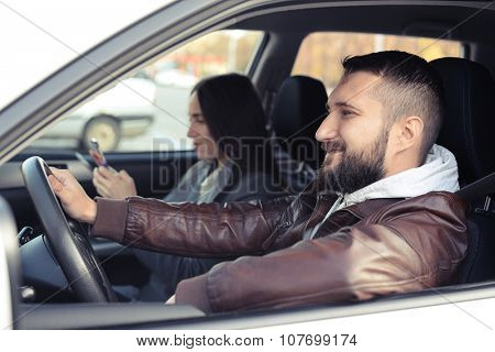 smiley young man driving the car, woman chatting on smartphone