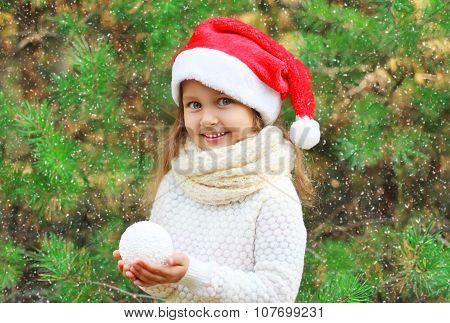 Christmas And People Concept - Little Smiling Girl Child In Santa Red Hat With Snowball