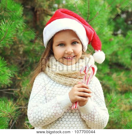 Christmas And People Concept - Portrait Little Smiling Girl Child In Santa Red Hat With Sweet Lollip