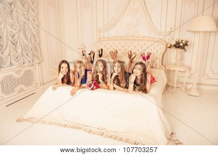 Happy Girls Celebrating A Bachelorette Party Of Bride Liying On The Bed