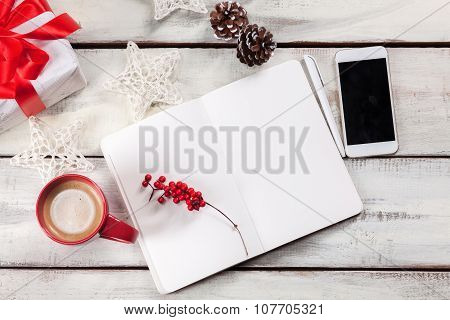The open notebook on the wooden table with a phone