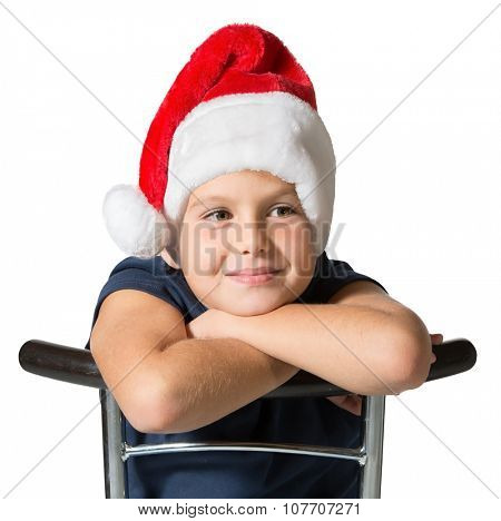 Photo executed on a white background. Charming seven-year boy in Santa Claus hat smiling