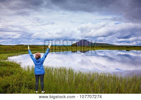 The woman - tourist in blue jacket raised her hands in delight beauty of nature. Blue lake water reflects the snowy hills. Iceland
