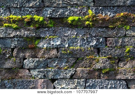 Wall made of natural stones with the growing moss