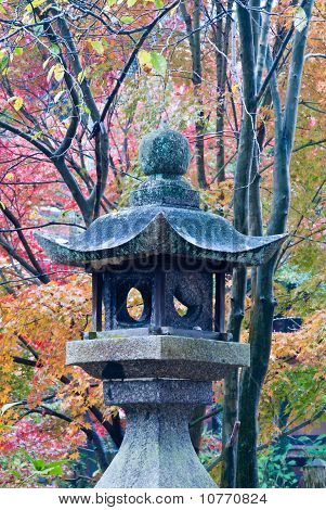 Stone Lantern Shot Against A Colorful Background Of Fall Foliage (portrait)