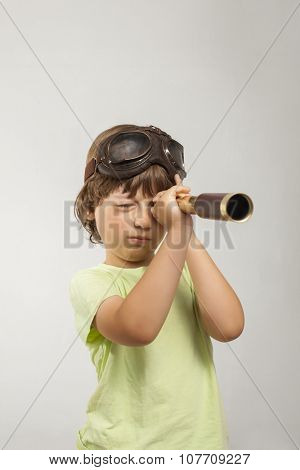 happy boy looks through a telescope