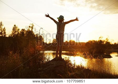 Happy Girl Standing On A Rock At Sunset