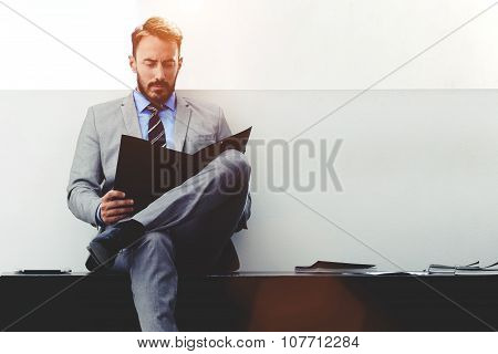 Confident man lawyer in formal wear reading paper documents while sitting in modern office