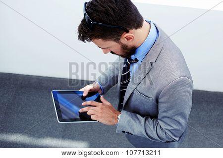 Young successful entrepreneur dressed in luxury suit working on digital tablet during work break