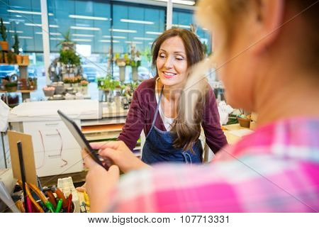Florist looking at female customer using digital tablet in flower shop