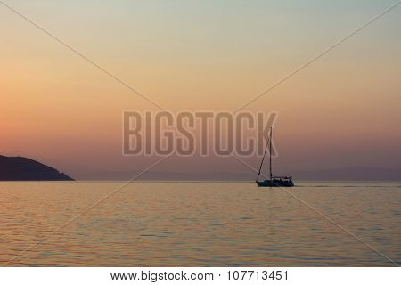 Small bat sails on the sea at sunset