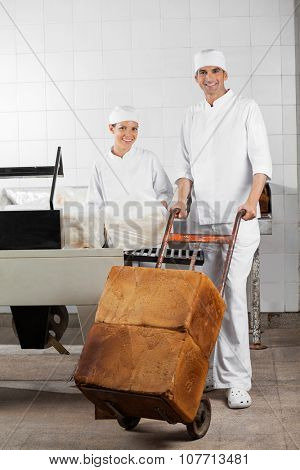 Portrait of confident male worker pushing bread loaves on pushcart while colleague smiling in bakery