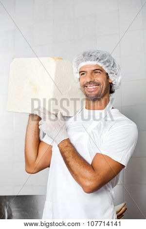 Happy mid adult male baker carrying big bread loaf on shoulder in bakery