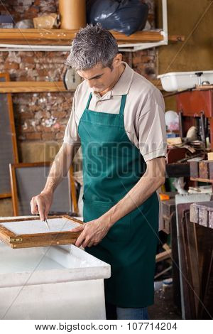 Mature male worker cleaning paper with tweezers in factory
