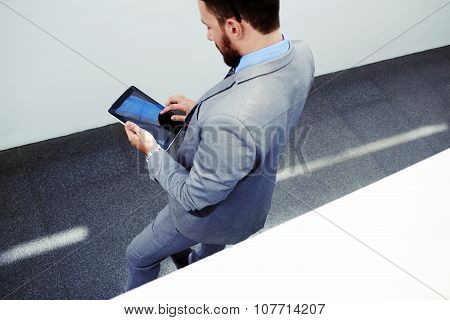 Successful man in formal wear reading news on his digital tablet during work break