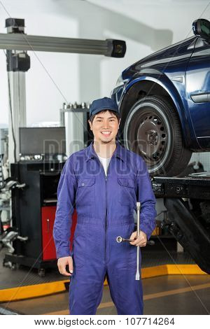 Portrait of happy mechanic holding rim wrench while standing at garage