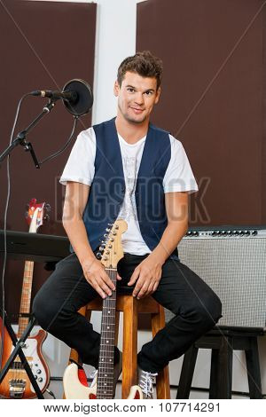 Full length portrait of confident man holding guitar while sitting on stool in recording studio