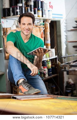Portrait of confident worker holding digital tablet while sitting in paper factory