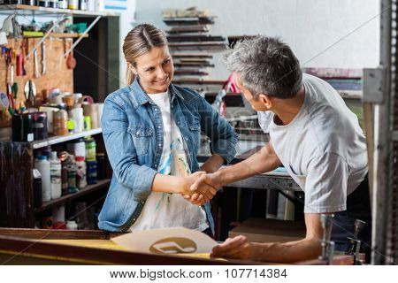 Smiling female worker shaking hands with male colleague in factory