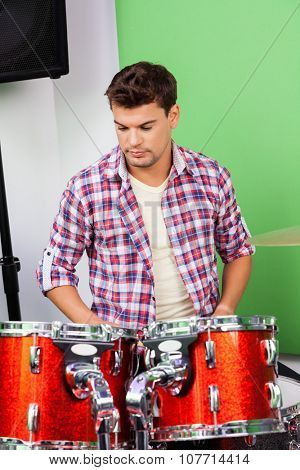 Young man looking at drums in recording studio