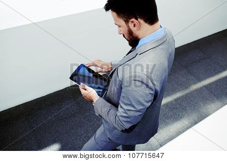 View from above of a smart University Professor reading electronic book on touch pad before lectures