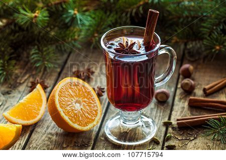 Mulled wine traditional hot spiced alcohol beverage in glass cup with orange, cinnamon, anise and ot
