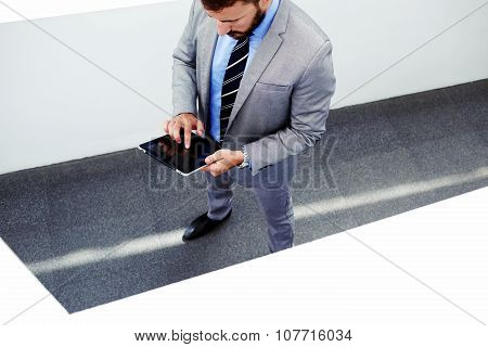Portrait of young confident man lawyer holding digital tablet with copy space screen for your text