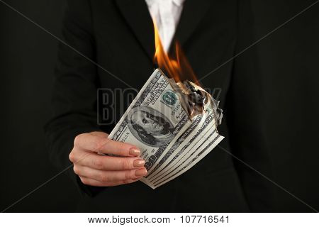 Woman burning  dollars closeup