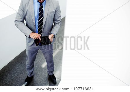 Smart male professional worker using touch pad while standing in office space