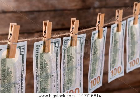 Concept of money laundering - dollars are drying on cord on wooden background, close up