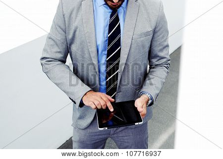 Young male skilled managing director in luxury suit using digital tablet during work break