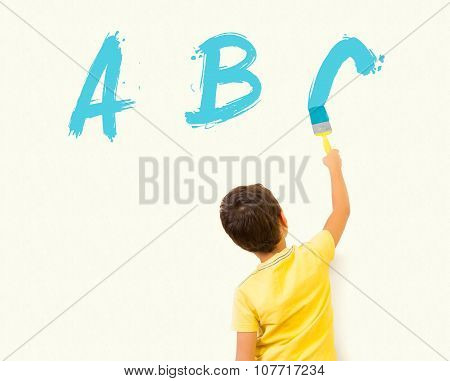 Little boy painting ABC with brush on the wall  - Almost Finished