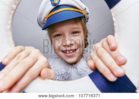 little girl in a captain's cap looking through life preserver.
