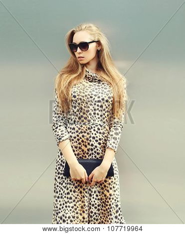 Beautiful Blonde Woman Wearing A Leopard Dress And Sunglasses With Handbag Clutch In The City