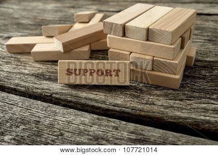 Wooden Block With Support Word Leaning On A Structure Made Of Many Other Blocks