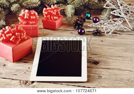 On The Wooden Table White Tablet With Christmas Presents Closeup