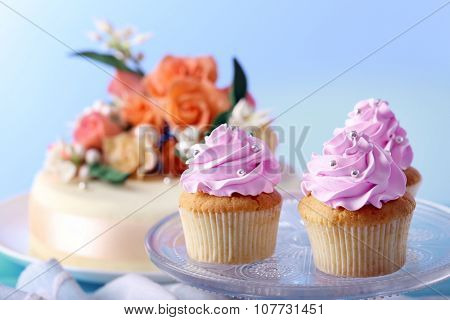 Tasty cupcakes on stand and cake, on table, on color background